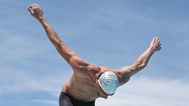 El nadador estadounidense Michael Phelps gira los brazos al menos tres veces antes de empezar una carrera.
