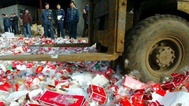 En esta foto de 2004, se observa a las autoridades chinas destruyendo un cargamento de cigarrillos falsificados.