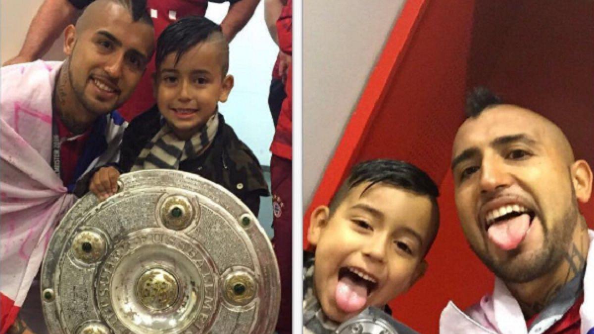 Arturo Vidal festeja levantando el trofeo de campeón junto a su hijo en Alemania