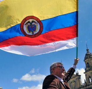 La bandera de Colombia con dos franjas más, una arriba y una abajo, de color blanco, símbolo universal de la paz.