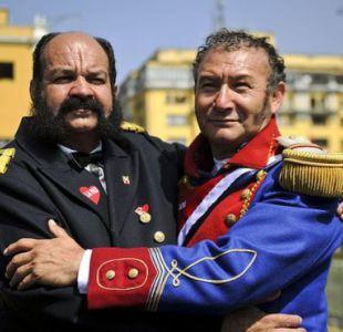 Dos hombres disfrazados como el héroe peruano Miguel Grau y el prócer chileno Bernardo O'Higgins abrazados en una plaza en Perú.