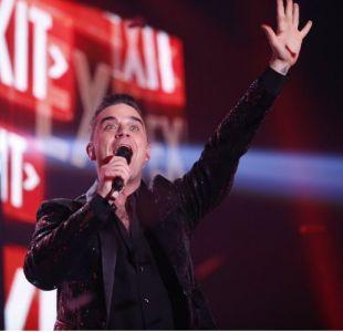 Robbie Williams se limpia las manos después de saludar a los fans