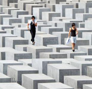 Dos visitantes caminan sobre los pilares del monumento al Holocausto en Berlín.