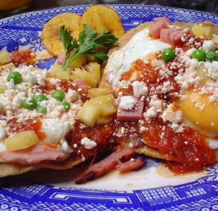 Una delicia de Yucatán: huevos motuleños, que son fritos y servidos sobre una tostada con frijoles negros, salsa de tomate, jamón y chícharos, con plátano, queso y salsa picante.