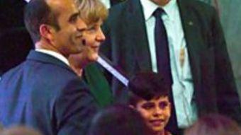 """Niño afgano le quiere agarrar la mano a Angela Merkel para """"agradecerle"""" por su vida en Alemania"""